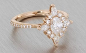 Oval diamond ballerina ring set with an array of pear shapes and round brilliant diamond around the centre stone