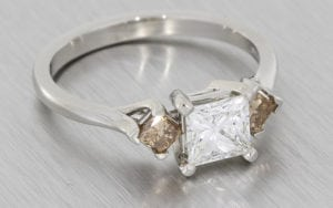 Platinum princess cut three stone ring set with champagne diamonds on the shoulders