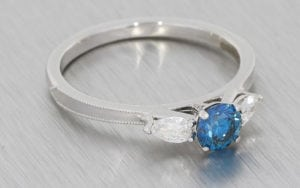 Three stone ring featuring a treated blue diamond,  framed With stunning pear shaped diamonds