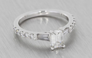Art Deco style platinum ring with a step cut diamond trilogy and diamond set shoulders