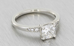 Incredible cushion cut diamond platinum ring with diamond set shoulders