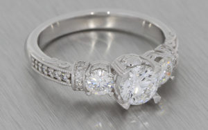 18K white three stone diamond ring with grain set shoulders