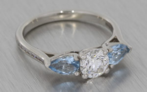 Palladium three stone, round diamond and pear shape aquamarine ring