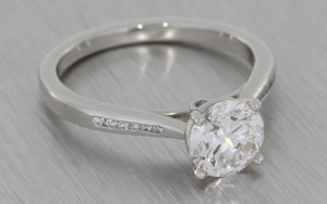 Platinum solitaire engagement ring set with a round brilliant diamond and channel set shoulders